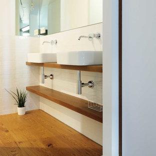 Foto di una stanza da bagno padronale scandinava di medie dimensioni con doccia a filo pavimento, WC sospeso, piastrelle verdi, piastrelle in gres porcellanato, pareti bianche, pavimento con piastrelle a mosaico, lavabo a bacinella, top in legno, pavimento verde e top marrone