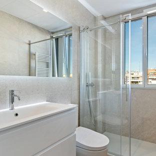 Modelo de cuarto de baño con ducha, actual, de tamaño medio, con armarios con paneles lisos, puertas de armario blancas, ducha empotrada, sanitario de una pieza, baldosas y/o azulejos grises, lavabo integrado, suelo beige, ducha con puerta con bisagras y encimeras blancas