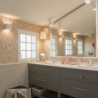 Immagine di una grande stanza da bagno per bambini shabby-chic style con ante con bugna sagomata, ante grigie, doccia alcova, WC sospeso, piastrelle rosa, pareti rosa, pavimento in laminato, lavabo sottopiano, top in quarzo composito e porta doccia a battente