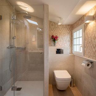 Großes Modernes Kinderbad mit profilierten Schrankfronten, grauen Schränken, Duschnische, Wandtoilette, beigefarbenen Fliesen, Keramikfliesen, beiger Wandfarbe, Laminat, Unterbauwaschbecken, Quarzwerkstein-Waschtisch und Falttür-Duschabtrennung in Bilbao