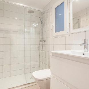 Diseño de cuarto de baño contemporáneo con armarios con paneles lisos, puertas de armario blancas, ducha empotrada, baldosas y/o azulejos blancos, lavabo integrado, suelo gris, ducha con puerta corredera y encimeras blancas