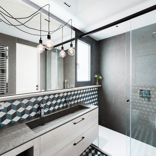 Modelo de cuarto de baño con ducha, contemporáneo, con armarios con paneles lisos, puertas de armario de madera clara, ducha empotrada, baldosas y/o azulejos grises, baldosas y/o azulejos multicolor, paredes grises, lavabo de seno grande, suelo multicolor, ducha con puerta corredera y encimeras grises