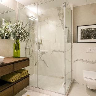 Diseño de cuarto de baño con ducha, minimalista, con armarios abiertos, puertas de armario de madera en tonos medios, ducha esquinera, sanitario de pared, baldosas y/o azulejos blancos, paredes grises, lavabo sobreencimera, encimera de madera, suelo gris, ducha con puerta con bisagras y encimeras marrones