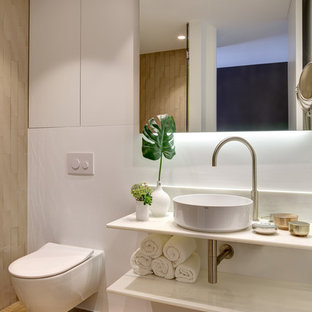 Foto de cuarto de baño con ducha, costero, con puertas de armario blancas, suelo de madera en tonos medios, lavabo sobreencimera, encimera de mármol, encimeras blancas, ducha empotrada, sanitario de pared, paredes blancas, suelo beige y ducha con puerta con bisagras
