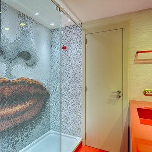 Modelo de cuarto de baño ecléctico con ducha empotrada, baldosas y/o azulejos multicolor, baldosas y/o azulejos en mosaico, paredes amarillas, lavabo integrado, suelo naranja, ducha con puerta corredera y encimeras naranjas