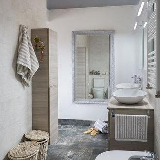 Modelo de cuarto de baño doble, con ducha y a medida, contemporáneo, de tamaño medio, con puertas de armario de madera clara, sanitario de pared, baldosas y/o azulejos beige, paredes blancas, lavabo sobreencimera, encimera de madera, suelo gris y encimeras beige