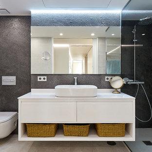 Ejemplo de cuarto de baño con ducha, actual, con puertas de armario blancas, ducha a ras de suelo, baldosas y/o azulejos grises, paredes negras, lavabo sobreencimera y encimeras blancas