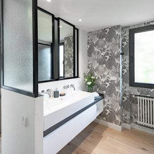 Diseño de cuarto de baño contemporáneo con armarios con paneles lisos, puertas de armario blancas, paredes grises, suelo de madera clara, lavabo de seno grande y suelo beige