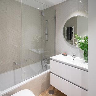 Ejemplo de cuarto de baño contemporáneo con armarios con paneles lisos, puertas de armario blancas, bañera empotrada, combinación de ducha y bañera, baldosas y/o azulejos grises, suelo de madera en tonos medios, suelo marrón, ducha abierta y encimeras blancas