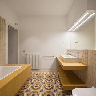 Ejemplo de cuarto de baño con ducha, mediterráneo, con puertas de armario amarillas, bañera encastrada, sanitario de pared, baldosas y/o azulejos beige, baldosas y/o azulejos de cemento, paredes blancas, lavabo de seno grande, suelo multicolor y encimeras amarillas