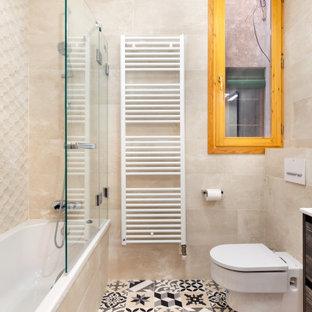 Modelo de cuarto de baño con ducha, contemporáneo, de tamaño medio, con armarios con paneles lisos, puertas de armario de madera oscura, bañera empotrada, combinación de ducha y bañera, sanitario de pared, baldosas y/o azulejos beige, baldosas y/o azulejos de porcelana, suelo de baldosas de porcelana, lavabo integrado, suelo multicolor y encimeras blancas
