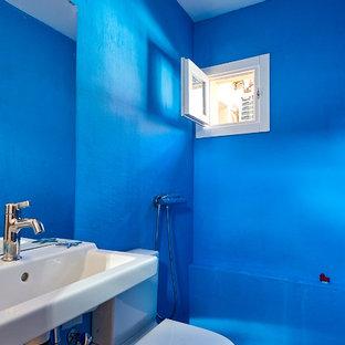 Foto de cuarto de baño mediterráneo con sanitario de dos piezas, paredes azules, lavabo suspendido y suelo gris
