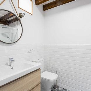 Industriell inredning av ett vit vitt badrum med dusch, med släta luckor, skåp i ljust trä, en toalettstol med hel cisternkåpa, vit kakel, tunnelbanekakel, vita väggar, cementgolv, ett konsol handfat och flerfärgat golv
