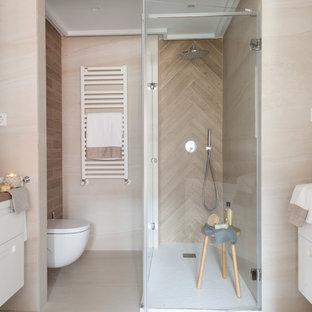 Imagen de cuarto de baño actual con armarios con paneles lisos, puertas de armario blancas, sanitario de pared, baldosas y/o azulejos beige, lavabo sobreencimera, encimera de madera, suelo beige, ducha con puerta con bisagras y encimeras marrones