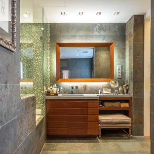 Modelo de cuarto de baño con ducha, mediterráneo, con armarios con paneles lisos, puertas de armario de madera oscura, bañera encastrada, ducha empotrada, baldosas y/o azulejos verdes, baldosas y/o azulejos en mosaico, paredes grises, lavabo integrado, suelo gris y ducha con puerta con bisagras
