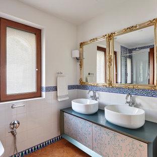 Modelo de cuarto de baño mediterráneo con armarios con paneles lisos, baldosas y/o azulejos blancos, paredes blancas, lavabo sobreencimera, encimeras azules y suelo marrón