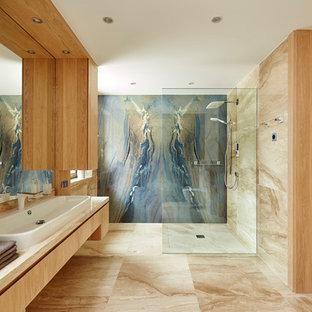 Ispirazione per una grande stanza da bagno padronale design con doccia a filo pavimento, pareti beige, lavabo a bacinella, ante lisce, ante in legno chiaro, piastrelle blu, lastra di pietra e doccia aperta