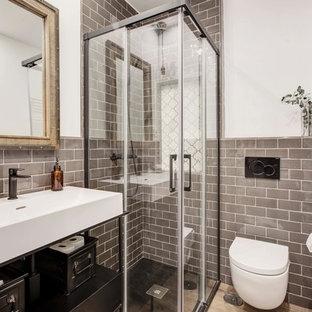 Idéer för att renovera ett litet industriellt vit vitt badrum med dusch, med en hörndusch, en vägghängd toalettstol, grå kakel, laminatgolv, ett avlångt handfat, bänkskiva i akrylsten, brunt golv, dusch med skjutdörr, tunnelbanekakel och vita väggar