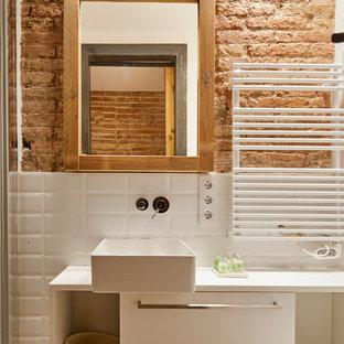 Foto de cuarto de baño industrial con armarios con paneles lisos, puertas de armario blancas, baldosas y/o azulejos blancos, baldosas y/o azulejos de cemento y lavabo sobreencimera