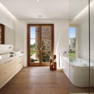 Modelo de cuarto de baño principal, mediterráneo, de tamaño medio, con lavabo sobreencimera, armarios con paneles lisos, puertas de armario beige, bañera exenta, paredes blancas, suelo de madera en tonos medios y suelo marrón