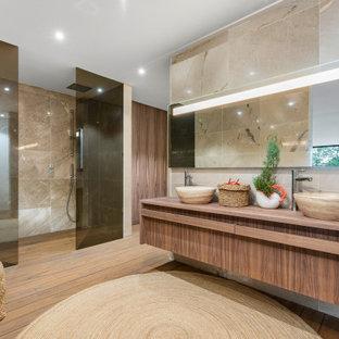 Foto de cuarto de baño principal, contemporáneo, extra grande, con armarios con paneles lisos, puertas de armario de madera oscura, ducha empotrada, baldosas y/o azulejos beige, paredes beige, lavabo sobreencimera, encimera de madera, suelo marrón y encimeras marrones