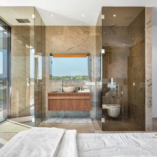 Foto de cuarto de baño principal, actual, grande, con armarios con paneles lisos, puertas de armario de madera oscura, ducha abierta, sanitario de pared, baldosas y/o azulejos beige, paredes blancas, lavabo sobreencimera, encimera de madera, suelo beige, ducha con puerta con bisagras y encimeras marrones