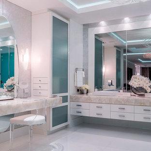 Inredning av ett modernt badrum, med släta luckor, vita skåp, vita väggar, bambugolv, ett fristående handfat och vitt golv