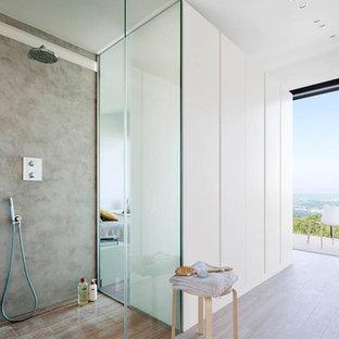 Modelo de cuarto de baño con ducha, moderno, de tamaño medio, con ducha abierta, paredes blancas, suelo de madera en tonos medios y ducha abierta