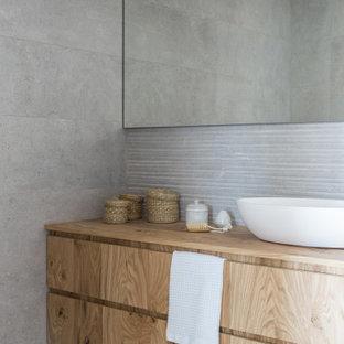 Idéer för att renovera ett litet skandinaviskt brun brunt badrum med dusch, med möbel-liknande, skåp i mellenmörkt trä, en dusch i en alkov, ett urinoar, grå kakel, keramikplattor, grå väggar, cementgolv, ett fristående handfat, träbänkskiva, grått golv och dusch med gångjärnsdörr