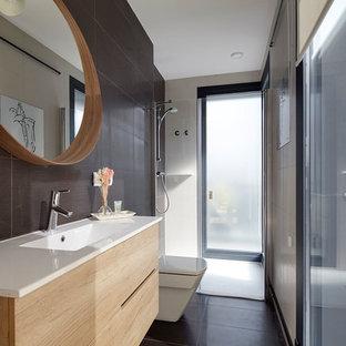 Ejemplo de cuarto de baño con ducha, moderno, pequeño, con armarios con paneles lisos, puertas de armario de madera clara, ducha a ras de suelo, paredes negras, lavabo integrado, ducha con puerta con bisagras y encimeras blancas