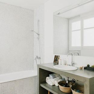 Foto de cuarto de baño principal, actual, de tamaño medio, con armarios abiertos, combinación de ducha y bañera, paredes blancas, baldosas y/o azulejos blancos, lavabo encastrado, encimera de cemento y suelo blanco