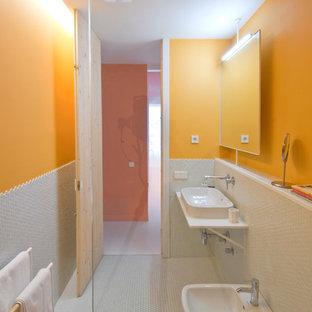 Ispirazione per una stanza da bagno con doccia design di medie dimensioni con doccia a filo pavimento, bidè, pareti arancioni e lavabo sospeso