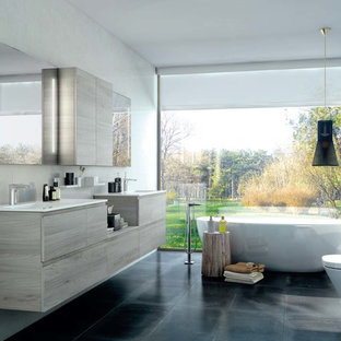 Mid-sized contemporary master bathroom in Other with flat-panel cabinets, medium wood cabinets, a freestanding tub, a wall-mount toilet, white walls and an integrated sink.