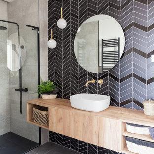 Diseño de cuarto de baño con ducha, contemporáneo, con armarios con paneles lisos, puertas de armario de madera clara, ducha a ras de suelo, lavabo sobreencimera, encimera de madera, suelo gris y encimeras marrones