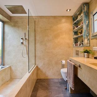 Foto de cuarto de baño microcemento, actual, con puertas de armario beige, combinación de ducha y bañera, lavabo integrado, bañera esquinera, paredes beige, suelo de cemento, suelo marrón, ducha abierta y encimeras beige