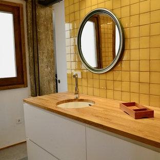 Неиссякаемый источник вдохновения для домашнего уюта: главная ванная комната среднего размера в стиле лофт с фасадами островного типа, белыми фасадами, накладной ванной, инсталляцией, желтой плиткой, керамической плиткой, желтыми стенами, бетонным полом, врезной раковиной, столешницей из дерева, серым полом и коричневой столешницей
