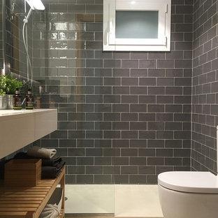 Exemple d'une petit salle de bain principale chic avec une douche à l'italienne, un urinoir, un carrelage gris, un carrelage métro, un mur blanc, un sol en terrazzo, un lavabo encastré et un plan de toilette en surface solide.
