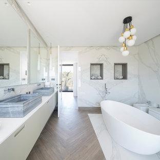 Ejemplo de cuarto de baño principal, contemporáneo, grande, con bañera exenta, sanitario de pared, baldosas y/o azulejos blancos, paredes blancas, suelo de madera en tonos medios, lavabo sobreencimera, suelo marrón, armarios con paneles lisos, puertas de armario beige y encimeras blancas