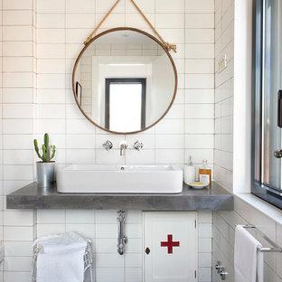 Modelo de cuarto de baño nórdico, de tamaño medio, con paredes blancas, suelo de cemento, lavabo sobreencimera, suelo negro y encimeras grises