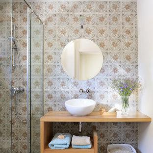 Imagen de cuarto de baño con ducha, actual, de tamaño medio, con armarios abiertos, puertas de armario de madera oscura, paredes multicolor, lavabo sobreencimera, encimera de madera y ducha con puerta corredera