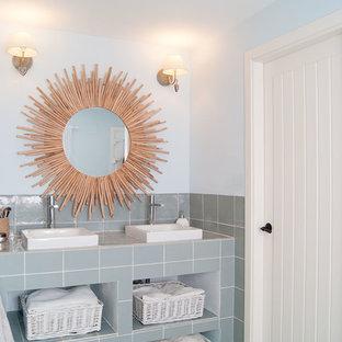 他の地域の地中海スタイルのおしゃれな浴室 (セラミックタイル、オープンシェルフ、グレーのタイル、青い壁、ベッセル式洗面器、タイルの洗面台、ターコイズの床、グレーの洗面カウンター) の写真