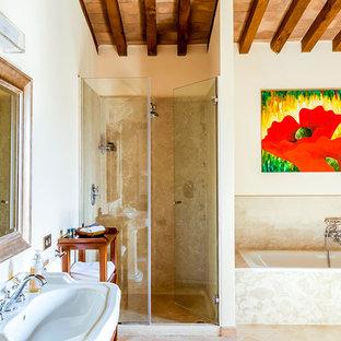 Modelo de cuarto de baño principal, mediterráneo, con armarios abiertos, puertas de armario de madera oscura, bañera encastrada, ducha empotrada, baldosas y/o azulejos de travertino, paredes beige, suelo de baldosas de terracota, lavabo con pedestal, suelo beige y ducha con puerta con bisagras