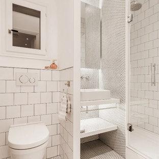 Foto de cuarto de baño con ducha, mediterráneo, de tamaño medio, con puertas de armario blancas, baldosas y/o azulejos blancos, baldosas y/o azulejos en mosaico, paredes blancas, encimeras blancas, lavabo sobreencimera, suelo blanco, ducha empotrada, sanitario de pared, suelo con mosaicos de baldosas y ducha con puerta con bisagras