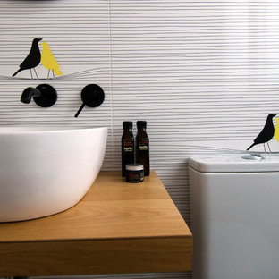 This is an example of a medium sized mediterranean bathroom in Valencia with recessed-panel cabinets, beige cabinets, a one-piece toilet, black and white tiles, porcelain tiles, light hardwood flooring, a vessel sink and laminate worktops.