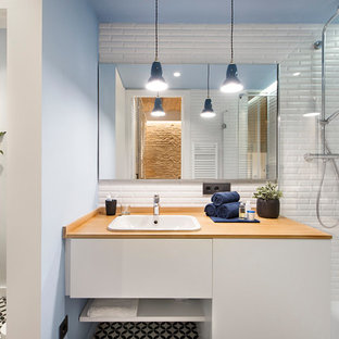 Photo of a medium sized mediterranean shower room bathroom in Madrid with flat-panel cabinets, white cabinets, a wall mounted toilet, white walls, ceramic flooring, wooden worktops, multi-coloured floors, white tiles, a built-in sink and brown worktops.