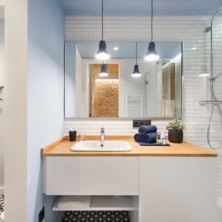 Imagen de cuarto de baño con ducha, mediterráneo, de tamaño medio, con armarios con paneles lisos, puertas de armario blancas, sanitario de pared, paredes blancas, suelo de baldosas de cerámica, encimera de madera, suelo multicolor, baldosas y/o azulejos blancos, lavabo encastrado y encimeras marrones