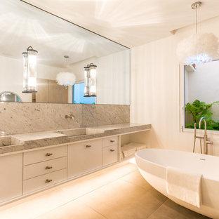 Ejemplo de cuarto de baño actual con armarios con paneles lisos, puertas de armario blancas, bañera exenta, paredes blancas, suelo de cemento, lavabo integrado, encimera de mármol, suelo gris y encimeras grises