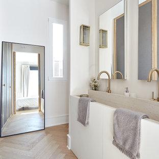 Imagen de cuarto de baño contemporáneo con armarios con paneles lisos, puertas de armario blancas, paredes blancas, suelo de madera clara, lavabo de seno grande y suelo beige
