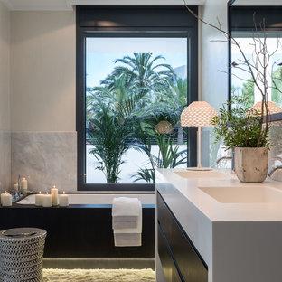 Foto på ett mellanstort funkis en-suite badrum, med släta luckor, svarta skåp, ett badkar i en alkov, svart och vit kakel, stenhäll, vita väggar, ett integrerad handfat och bänkskiva i akrylsten