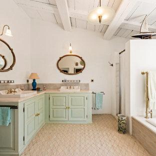 Diseño de cuarto de baño doble, a medida y abovedado, mediterráneo, con armarios con paneles con relieve, puertas de armario verdes, bañera encastrada, ducha empotrada, paredes blancas, lavabo encastrado, suelo beige, ducha con cortina y encimeras beige